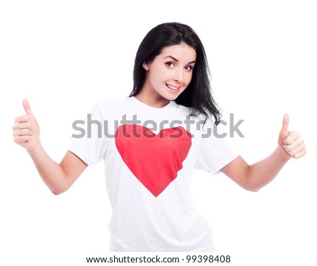 excited young woman wearing a T-shirt with a big red heart and  and showing two thumbs up, isolated against white background - stock photo