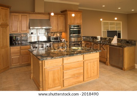 Expensive kitchen with granite counters and tile floor - stock photo