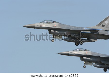 2 f16's flying in formation at an airshow. - stock photo