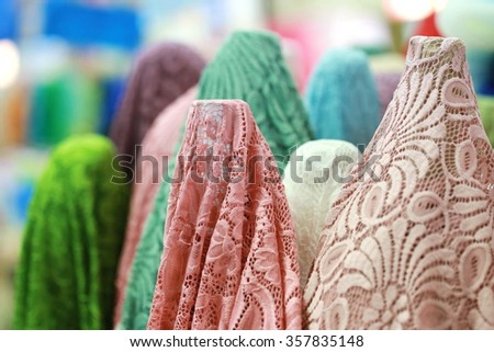 fabric roll in shop, pink lace fabric rolls in fabric shop background - stock photo