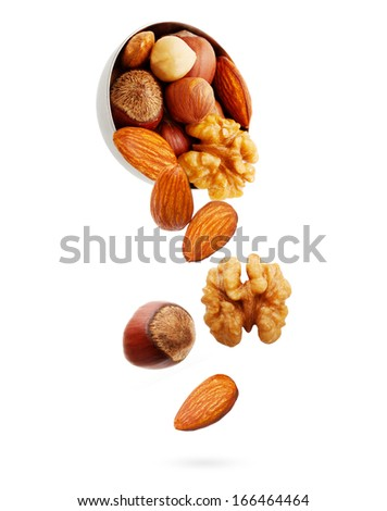Falling nuts in bowl isolated on white background. - stock photo