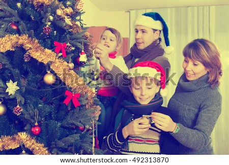 family at christmas time or winter holiday season - People Decorating A Christmas Tree
