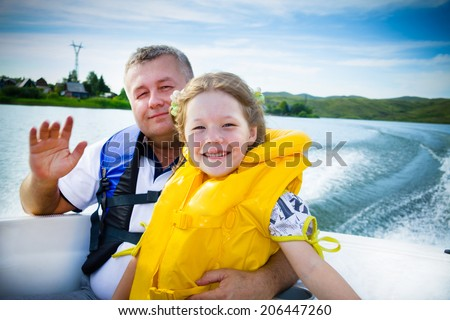 family by the boat on the river in a sunny day. - stock photo