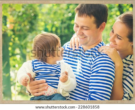 family father and mother playing with baby on nature vintage card  - stock photo