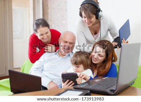 family of three generations uses few various electronic devices in home interior