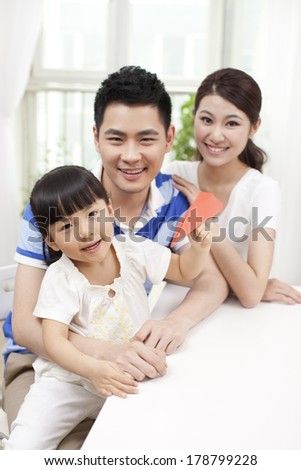 Family of three playing paper airplane - stock photo