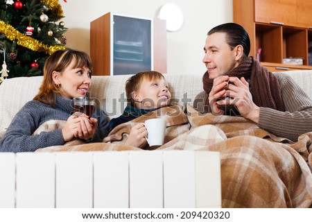 family of three with cups of tea warming near warm radiator in Christmas time at home - stock photo