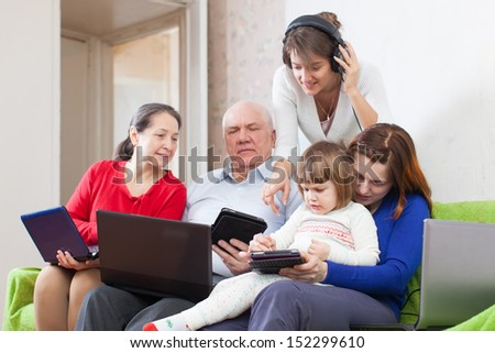 family of with few various portable computers on sofa at home interior
