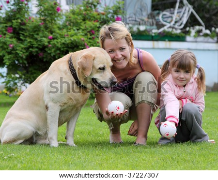 family plays with a dog a lawn at the house