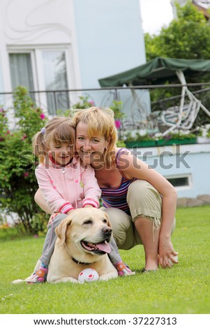 family plays with a dog a lawn at the house - stock photo