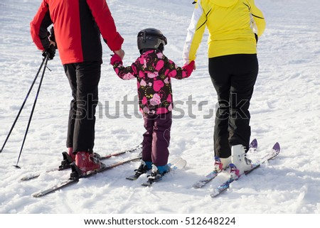 family riding on  alpine ski  at the winter resort