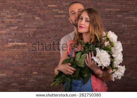 Family waiting for baby. Husband and wife with flowers in the studio. The theme of family relations and the expectation of the birth of the baby. - stock photo