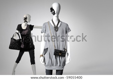 Fashion clothes on a mannequin holding bag on light background