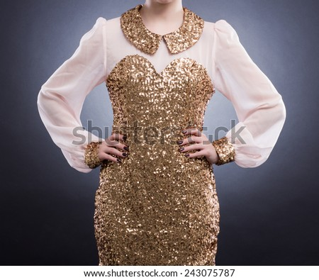 Fashion Image. Beautiful elegant dress with gold sequins on the young woman.