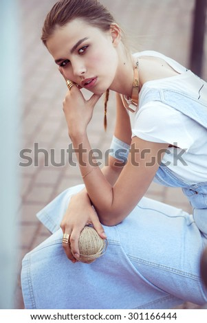 fashion model girl in jeans hat in her hand. outdoor color portrait