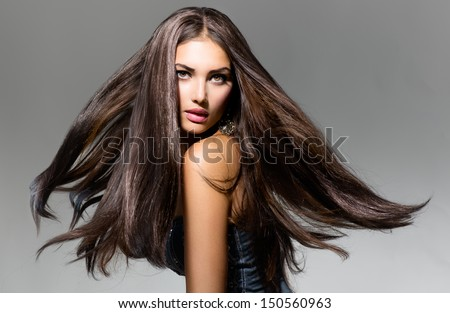 Fashion Model Girl Portrait with Long Blowing Hair. Glamour Beautiful Woman with Healthy and Beauty Brown Hair