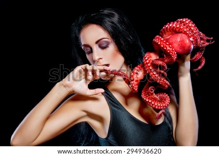 Fashion portrait. Halloween. Beautiful woman eats octopus. - stock photo