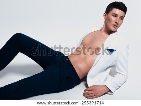 Fashion portrait of handsome young man in dark jeans and white jacket laying on the floor and looking to the left on white background  - stock photo