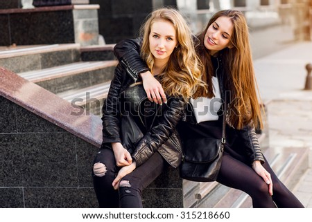 Fashion portrait of Two stylish pretty women posing on the street in sunny day. Wearing trendy urban outfit , leather jacket and boots heels. Young friends  waiting on stairs outdoor. - stock photo