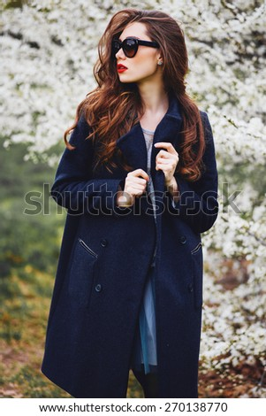 Fashion portrait of young pretty brunette model with red lips  in cool mirror  sunglasses,  wearing trendy    spring coat against  white blooming tree background. - stock photo