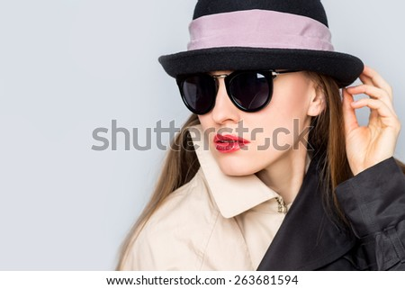 Fashion studio photo of stylish lady in hat and sunglasses looking sideways, copy space - stock photo