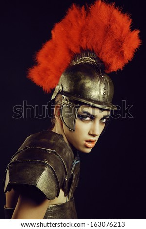 Fashion studio shot of beautiful woman in armor and in helmet with feathers on her head