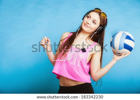 Fashion teen girl headphones listen music mp3 player. Fresh energetic young woman relax happy and dancing with ball blue background - stock photo