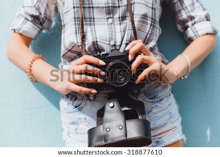 Fashionable beautiful happy stylish hipster girl, denim outfit,trendy woman outfit , cool vintage style, having fun, sitting, stairs, oldschool film camera, take photo, hands holding, blond, sneakers - stock photo