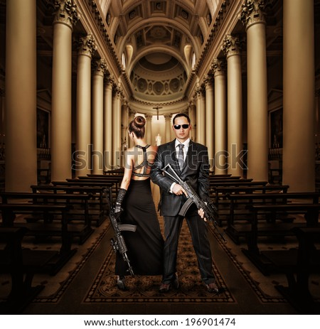 Fashionable couple - woman and man holding automatics in church - stock photo