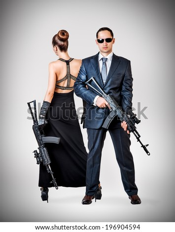 Fashionable couple - woman and man holding automatics on gray background