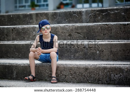 Fashionable little boy in sunglasses and cap siting on stone steps. Childhood.  Summertime.  - stock photo