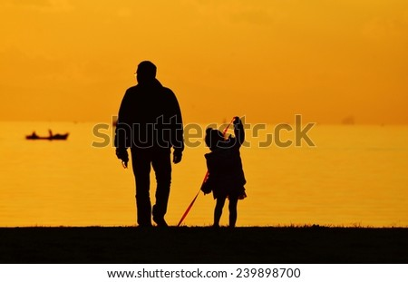 Father and daughter walking on seashore at sunset, silhouette. The girl playing with a ribbon.