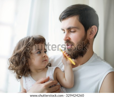 Father and little  daughter brushing their teeth in the bathroom