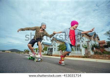 Father learning to ride skateboard as his son in the suburb street having fun - stock photo