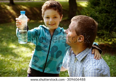 Father with his son in the green park,Son has a bottle of water in his hands,  - stock photo