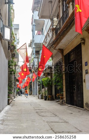 23 February, 2015 in Hanoi Vietnam, an alleyway with Vietnamese Flags and a boy is playing football.In Vietnam all the flag were out in the country in national festival as National Day, Lunar New Year