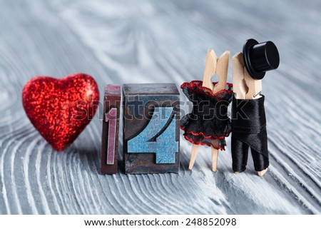 14 february. Valentines day. Romantic couple. Man, woman and read heart. Clothespins. (Soft focus, 14 written with colored vintage letterpress) - stock photo
