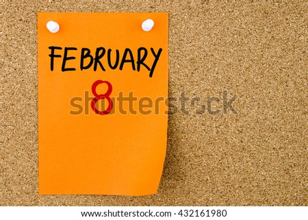 8 FEBRUARY written on orange paper note pinned on cork board with white thumbtacks, copy space available - stock photo