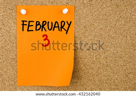 3 FEBRUARY written on orange paper note pinned on cork board with white thumbtacks, copy space available - stock photo