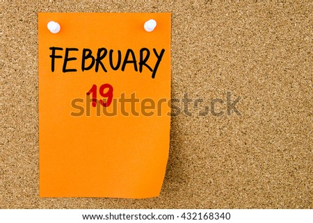 19 FEBRUARY written on orange paper note pinned on cork board with white thumbtacks, copy space available - stock photo