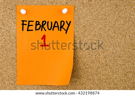 1 FEBRUARY written on orange paper note pinned on cork board with white thumbtacks, copy space available - stock photo