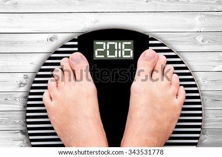 2016 feet on a weight scale on white wooden floor background - stock photo