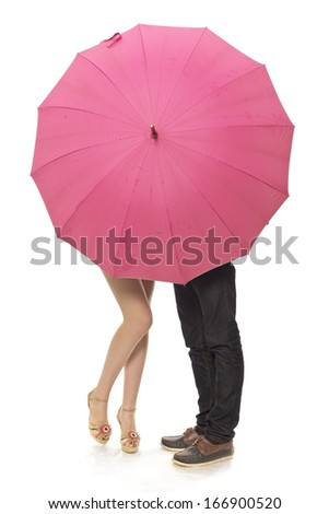 Female and man's legs under a umbrella - stock photo