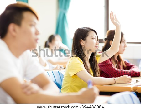female college student raise hand for question in classroom - stock photo