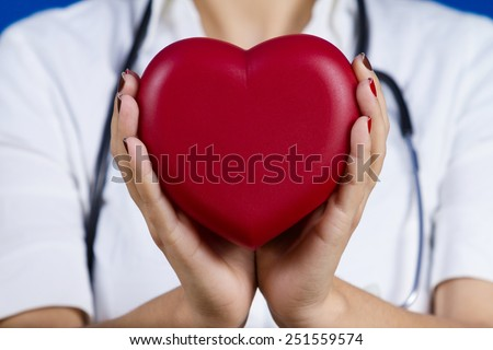 Female doctor holding red heart .Medicine,Health Care,Hospital. - stock photo