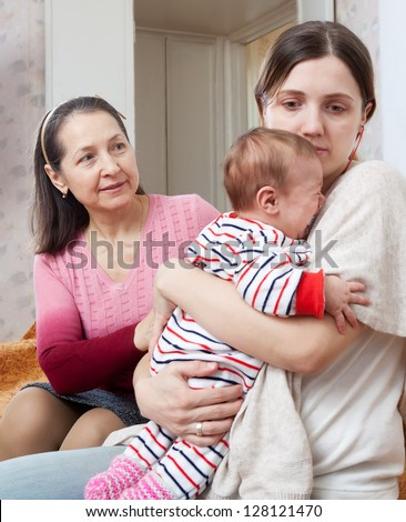 Female family problems. Mature woman tries reconcile with adult daughter with baby after conflict - stock photo