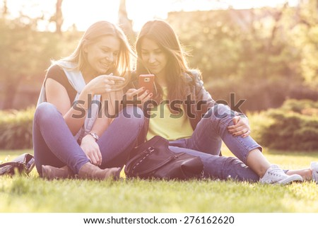 Female Friends Laughing and Looking at Cell Phone - stock photo