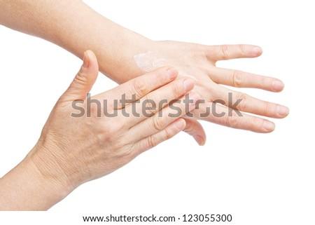 �Female hands applying hand cream isolated on white background - stock photo