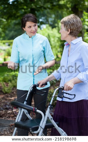 Female physiotherapist and senior woman with orthopedic walker outside - stock photo