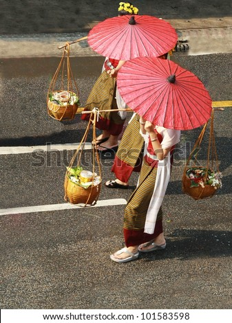 female shopkeeper in Thai old fashioned traditional cloth ,red paper umbrella and load Thai food  in bamboo basket walk on road, Thailand - stock photo